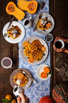 Petit-déjeuner avec gaufres à la citrouille et crème glacée, baies et chocolat