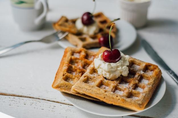 Petit-déjeuner avec gaufres et crème fouettée