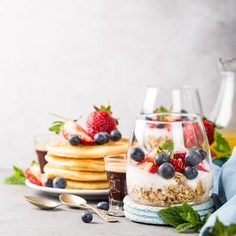 Petit déjeuner avec granola, crêpes et petits fruits