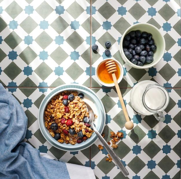 Petit-déjeuner avec granola et noix et myrtilles, miel et lait