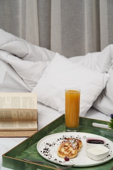Petit déjeuner à l'hôtel au lit. petit-déjeuner au service de l'hôtel avec jus de fruits frais, porridge et crêpes