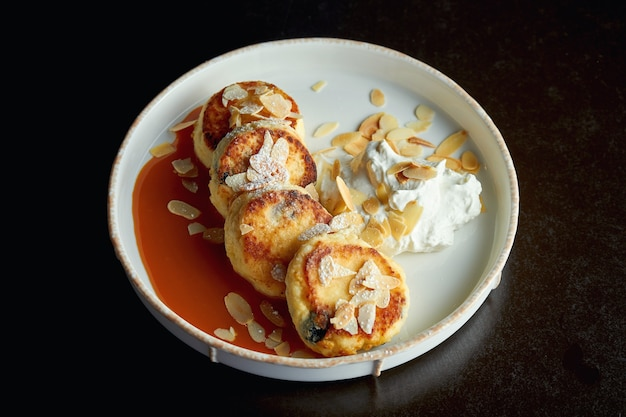 Un petit déjeuner idéal - crêpes au fromage cottage avec caramel, amandes et sauce à la crème dans une assiette blanche. ukrainien syrniki