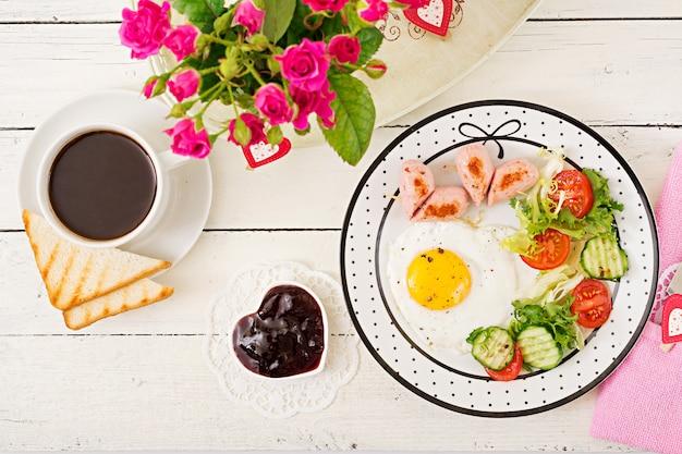 Petit déjeuner le jour de la saint-valentin - œuf au plat en forme de cœur, toasts, saucisses et légumes frais. tasse de café. petit déjeuner anglais. vue de dessus