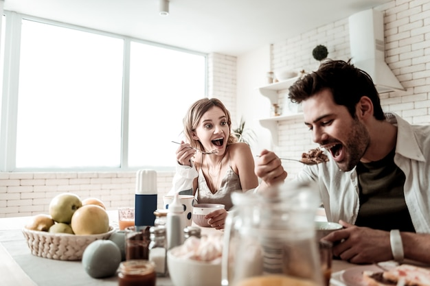 Petit déjeuner joyeux. barbu bel homme positif dans une chemise blanche se sentant merveilleux tout en mangeant le petit déjeuner avec sa femme