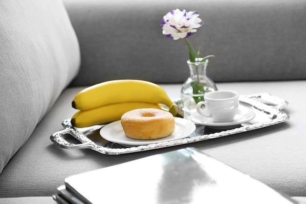 Petit-déjeuner léger et magazines sur canapé dans le salon, gros plan