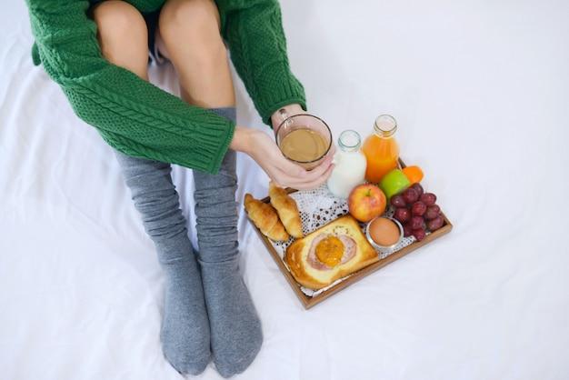 Petit déjeuner sur le lit avec café, croissants