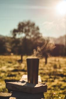 Petit-déjeuner avec un livre en plein air, couverture chaude, vapeur sur une tasse thermo