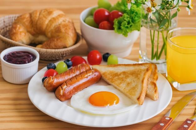 Petit-déjeuner maison avec œuf au plat, pain grillé, saucisse, fruits, légumes, confiture de fraises et orange