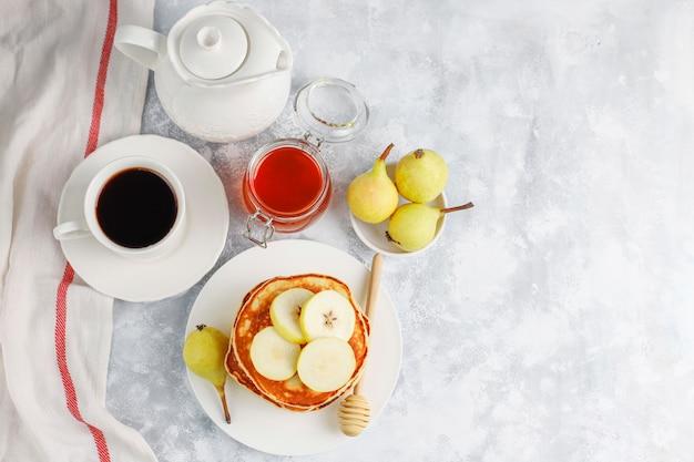 Petit déjeuner maison: pancakes de style américain servis avec des poires et du miel avec une tasse de thé sur du béton. vue de dessus et copie