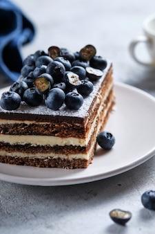 Petit déjeuner le matin avec café et gâteau. morceau de gâteau sur une assiette décorée de bleuets frais