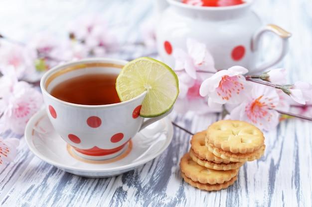 Petit déjeuner le matin de thé dans une tasse de petits pois colorés avec des biscuits