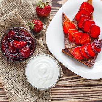 Petit déjeuner le matin. toasts à la fraise et à la confiture. pain et confiture. toasts chauds frais avec de la crème. délicieux dessert fait maison.