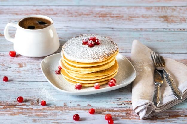 Petit-déjeuner matinal composé de crêpes aux canneberges et de sucre en poudre et d'une tasse de café sur une table en bois.