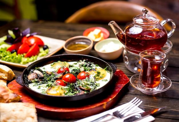 Petit déjeuner mis oeufs beurre de tomate miel pot de thé vue latérale
