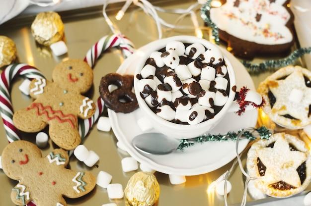 Petit-déjeuner de noël chocolat chaud, guimauve, bonhomme en pain d'épice, bonbons, biscuits et tarte hachée