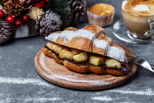 Petit-déjeuner de noël: croissant au chocolat et banane au four.