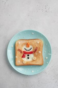 Petit-déjeuner de noël: pain grillé avec du blanc d'oeuf en forme de bonhomme de neige heureux