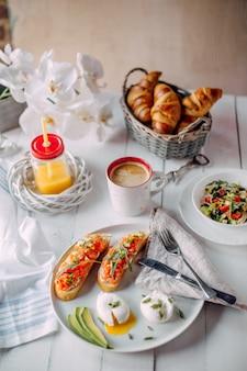 Petit déjeuner norvégien. toasts au saumon, œufs à la coque sur une table en bois blanc avec salade, café, jus d'orange et croissants