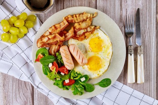 Petit-déjeuner nutritionnel avec œufs, hot-dogs, bacon et salade.