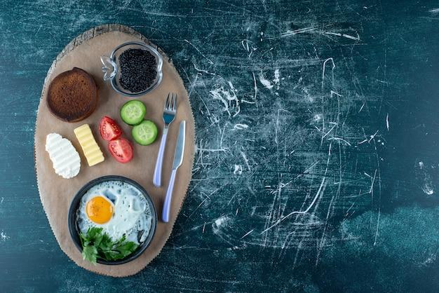 Petit déjeuner avec œuf au plat, caviar et légumes. photo de haute qualité