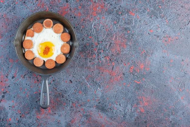 Petit déjeuner avec oeuf au plat et saucisses.