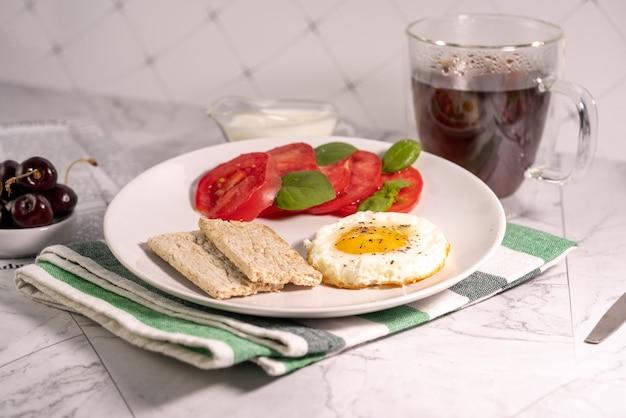 Petit-déjeuner avec œuf au plat, tomates et pain croustillant sur une assiette avec un verre sur une table