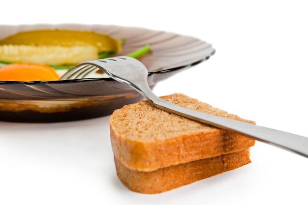 Petit déjeuner oeufs au plat sur une plaque de verre, avec un concombre mariné, des oignons frais et du pain de seigle