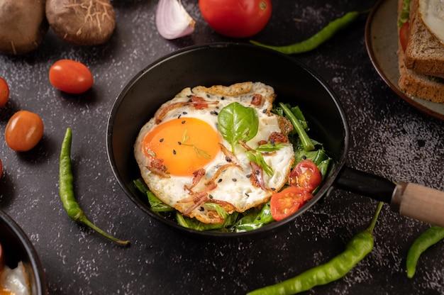 Petit-déjeuner avec des œufs au plat, des saucisses et du jambon dans une poêle avec des tomates. chili et basilic