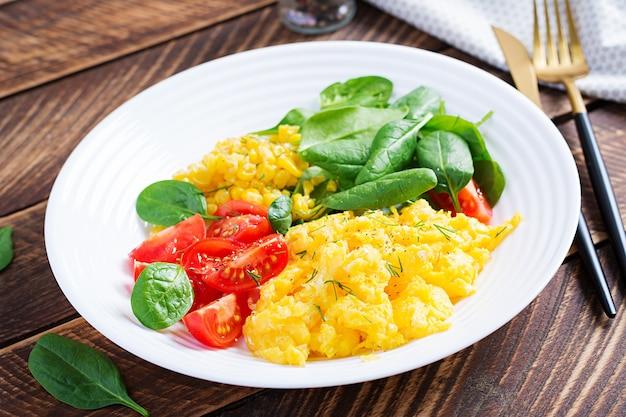 Petit-déjeuner. œufs brouillés aux tomates cerises, épinards et maïs.