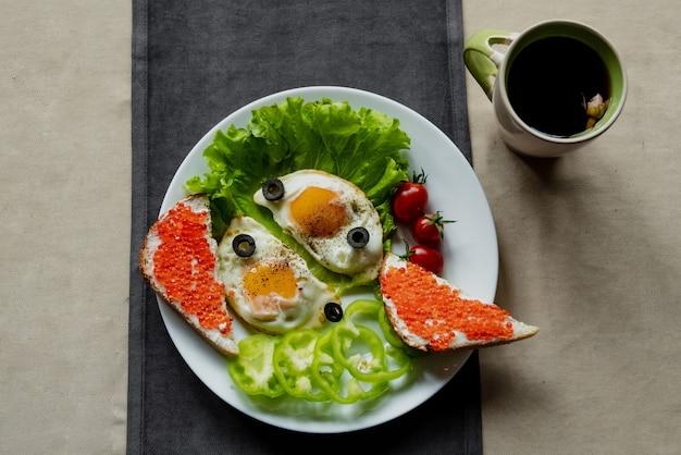 Petit-déjeuner, œufs brouillés sur feuilles de laitue, à côté de légumes frais et un sandwich au caviar rouge