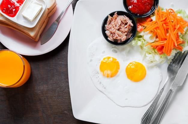 Petit déjeuner avec des œufs frits, des saucisses, du pain tranché avec de la confiture de fraises
