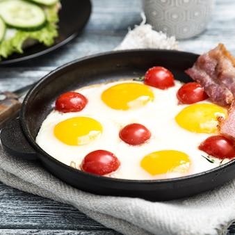 Petit-déjeuner avec des œufs, des tomates cerises, du bacon et des toasts grillés