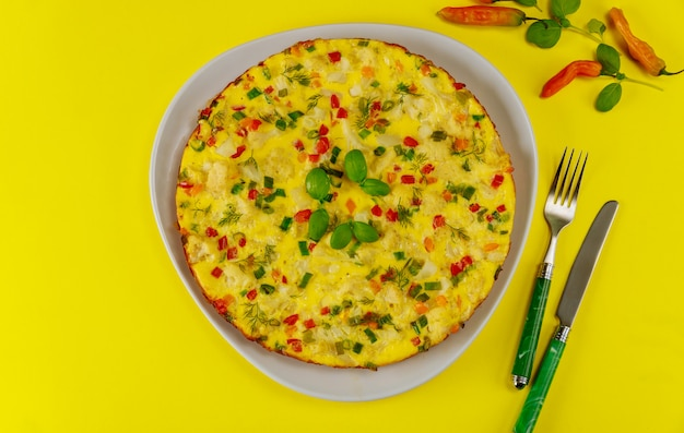 Petit déjeuner avec omelette aux légumes sur une surface jaune