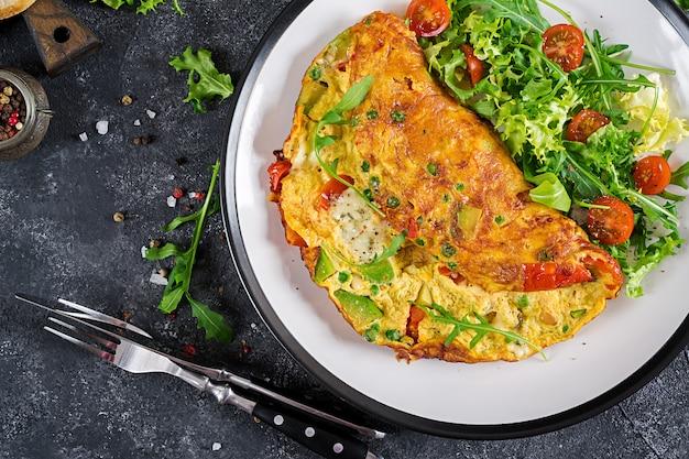 Petit déjeuner. omelette aux tomates, avocat, fromage bleu et petits pois sur une plaque blanche.