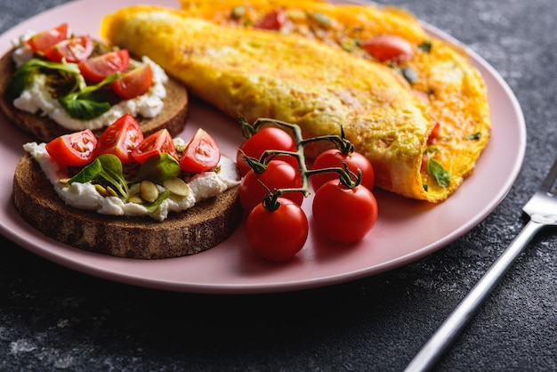 Petit-déjeuner avec omelette et pain aux céréales avec fromage à la crème, pesto et tomates cerises sur une plaque rose close-up