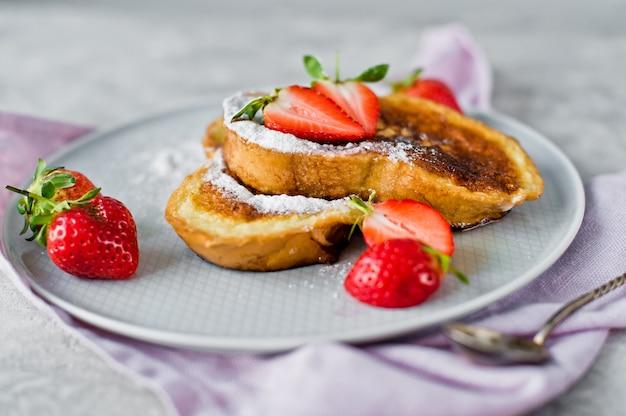 Petit déjeuner avec pain perdu et fraises.