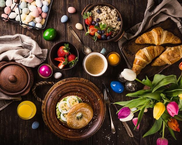 Petit-déjeuner de pâques rustique à plat avec des œufs, des bagels, des tulipes, des croissants, des œufs, des flocons d'avoine avec des baies, des œufs de caille colorés et des décorations de vacances de printemps. vue de dessus