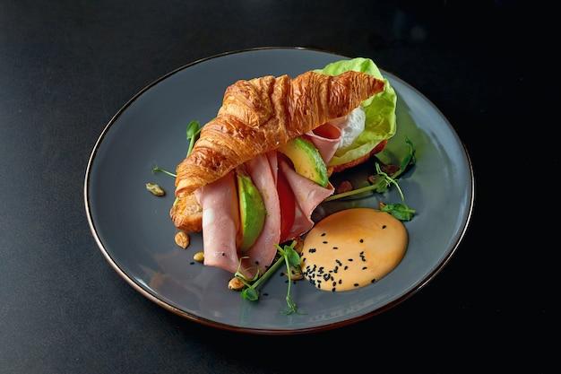 Petit-déjeuner parfait - sandwich au croissant avec saucisse à la mortadelle, avocat et sauce au fromage dans une assiette grise. mise au point sélective