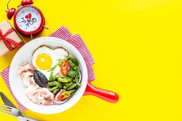 Petit-déjeuner pour votre bien-aimé pour les vacances: œuf en forme de cœur, bacon, haricots verts sur fond jaune. mise au point sélective. vue d'en-haut. copiez l'espace.
