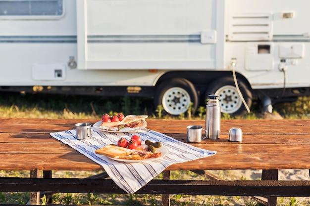 Petit-déjeuner près de la caravane œufs au plat avec du pain grillé au bacon et du café chaud dans un thermos