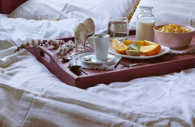 Petit déjeuner romantique au lit avec des fleurs de printemps. lumière de fenêtre, espace copie