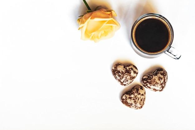 Petit-déjeuner romantique, café, gâteaux au chocolat en forme de cœur et une rose jaune sur fond blanc, espace de copie à plat