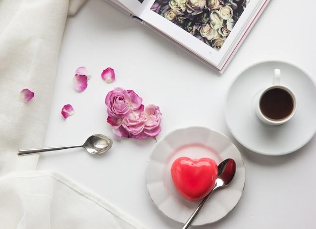 Petit-déjeuner romantique avec des gâteaux en forme de coeur et une tasse de café
