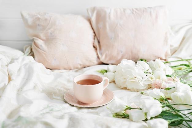 Petit-déjeuner romantique de la saint-valentin au lit avec tasse de thé et fleurs sur le lit