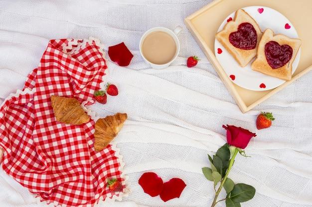 Petit-déjeuner romantique servi sur du tissu blanc