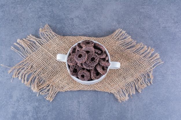 Petit-déjeuner sain avec des anneaux de maïs au chocolat dans une assiette sur une pierre.