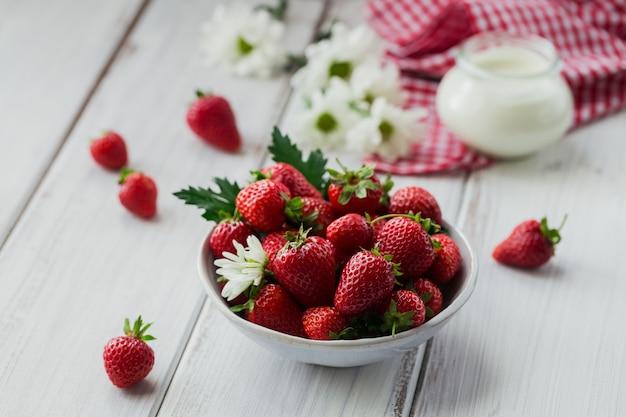 Petit-déjeuner sain avec des baies mûres et des produits laitiers. fraises fraîches dans un bol en céramique et yaourt bio naturel sur table en bois rustique blanc