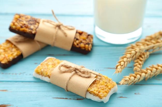 Petit-déjeuner sain avec des barres granola et du lait sur une table en bois bleue.