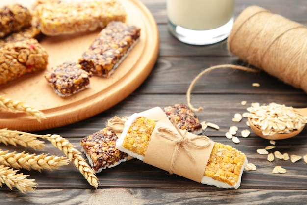 Petit-déjeuner sain avec barres granola et lait sur une table en bois marron.