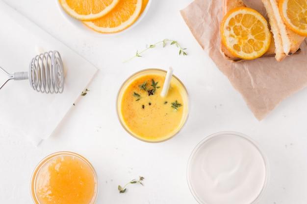 Petit-déjeuner sain à base de boisson lassi de mangue et de sandwichs. à côté d'un yaourt et de la confiture d'ingrédients blancs